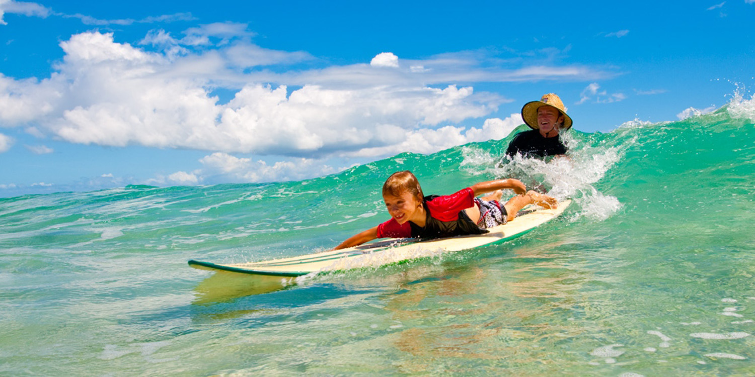 image of AARONTAIT COPYRIGHTED 2014 141 ADVERTISING LIFESTYLE BEACH ISLAND LIFE FATHER SON LEARNING TO SURF LAUGHTER LOVE PRIDE FUN MALIBU LONG BOARD