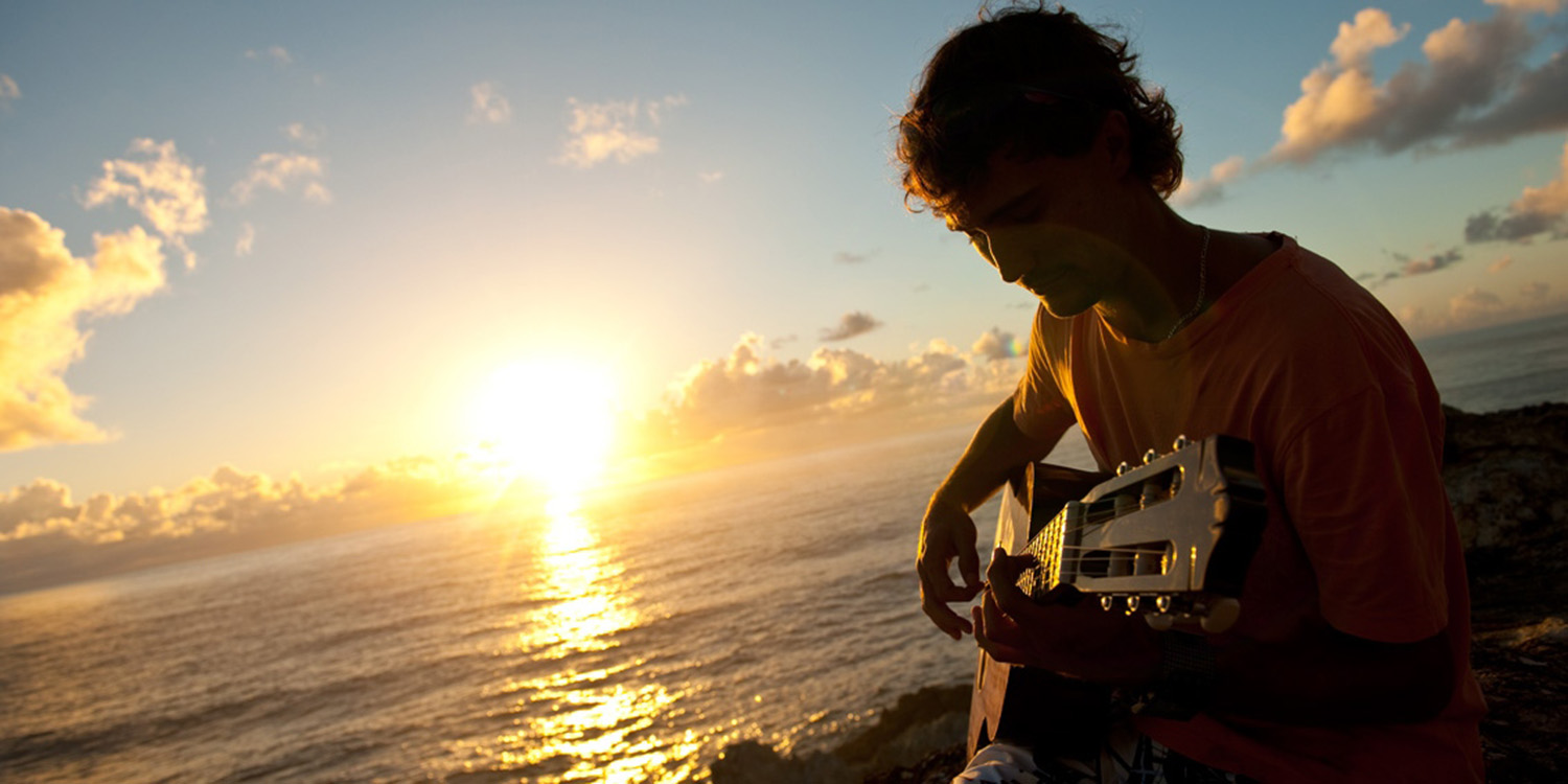 image of AARONTAIT COPYRIGHTED 2014 155 ADVERTISING LIFESTYLE BEACH ISLAND LIFE GUITARIST SUNRISE IN THE MOMENT WARM NATURAL LIGHT
